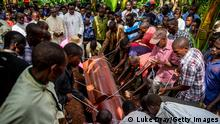 KAMWEZI, UGANDA - NOVEMBER 13: Men lower the coffin of John Bosco Tuhirirwe into his grave during his funeral on November 13, 2019 in Kamwezi, Uganda. John Bosco Tuhirirwe, was shot on November 10th, in the remote border town of Kamwezi, northern Rwanda. Tuhirirwe and four others, including Job Byarushaga, were stopped 200 metres from the Ugandan border by Rwandan forces while smuggling tobacco across the border on bicycles. According to eye-witnesses, both Byarushaga and Tuhirirwe tried to plead for forgiveness but Rwandan government forces, after finding they couldn't afford to pay a bribe, started shooting at the group killing both men on spot. His wife, Ayeba Allah, said that her husband, a farmer, had only been smuggling tobacco across the border for two months after a ban on selling and importing goods to Rwandans at the nearby crossing had greatly affected them, leaving them unable to pay school fees for their three children.His Uncle, Baketonda Ignitiou, also the Village Chief said ''How can a man fight the policemen without a gun. Why didn't they arrest him or put him in the courts of law so the judge can make him pay a fine instead of just killing an un-armed man? A long-term diplomatic dispute between Rwanda and Uganda has stopped almost all local border movements between the two countries, affecting the daily life of families on both sides. Only Ugandan citizens are permitted to cross providing they are not trading or carrying commercial goods. Despite the Rwandan government imposing bans of goods crossing either way, reports suggest that citizens of both countries continue to cross the porous border to look for food; often with deadly consequences. (Photo by Luke Dray/Getty Images)