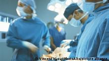 Doctors performing operation, surgeon's instruments in foreground || Modellfreigabe vorhanden
