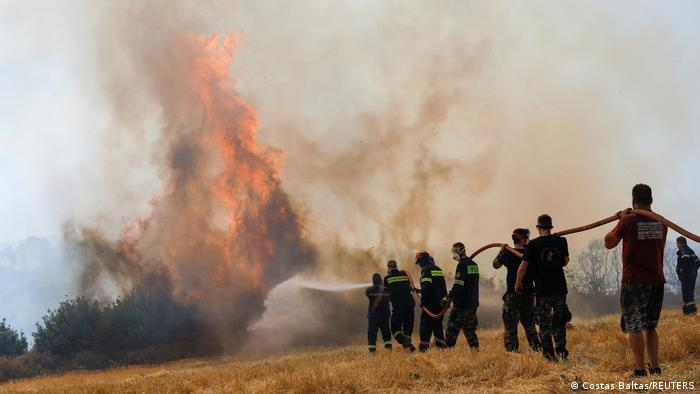 Firefighters and volunteers try to extinguish a wildfire burning north of Athens, Greece