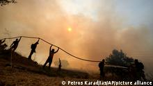 A firefighter tries to extinguish a fire as volunteers hold the water hose during a wildfire in Agios Stefanos, in northern Athens, Greece, Friday, Aug. 6, 2021. Thousands of people have fled wildfires burning out of control in Greece and Turkey, including a major blaze just north of the Greek capital of Athens that left one person dead. (AP Photo/Petros Karadjias)