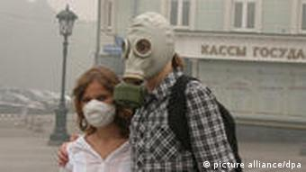 Two people wearing a gas mask and a surgical mask walk through the smoke in Moscow in July