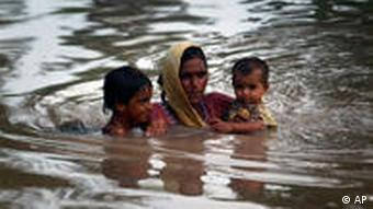 A Pakistani mother carries her children through floodwater