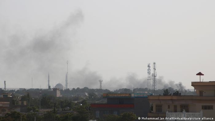 Foto mostra muita fumaça sobre uma cidade.