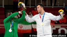 Silver medalist Tareg Hamedi of Saudi Arabia, left, and gold medalist Sajad Ganjzadeh of Iran stand together during the medal ceremony for men's kumite 75kg karate at the 2020 Summer Olympics, Saturday, Aug. 7, 2021, in Tokyo, Japan. (AP Photo/Vincent Thian)
