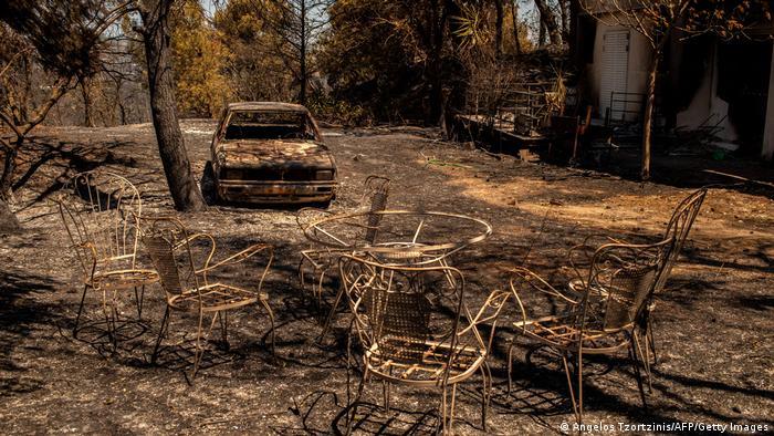Beschädigter Tisch und verbranntes Auto nach einem Lauffeuer im Norden Athens gefilmt