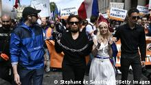 A protestor dressed in French Republic symbol Marianne marches with chains during a demonstration, part of a national day of protest against the mandatory Covid-19 health pass to access most of the public space, near Ecole Militaire in Paris on August 7, 2021. - A valid health pass is generated by two jabs from a recognised vaccine, a negative coronavirus test or a recent recovery from infection and has been validated for cafes and restaurants by the Constitutional Council on August 5, 2021. (Photo by STEPHANE DE SAKUTIN / AFP) (Photo by STEPHANE DE SAKUTIN/AFP via Getty Images)