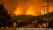 TOPSHOT - A local resident walks as a wildfire rages near the village of Gouves, on Euboea island, second largest Greek island, on August 8, 2021. - Hundreds of firefighters battled a blaze on the outskirts of Athens as several fires raged in Greece. (Photo by ANGELOS TZORTZINIS / AFP) (Photo by ANGELOS TZORTZINIS/AFP via Getty Images)