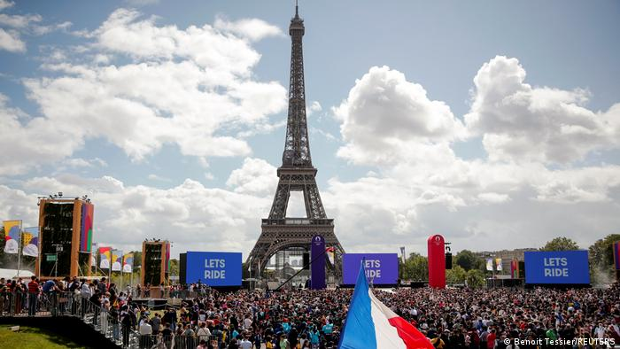 Foto mostra a Torre Eiffel e muitas pessoas na frente. É possível ver uma grande bandeira da França.