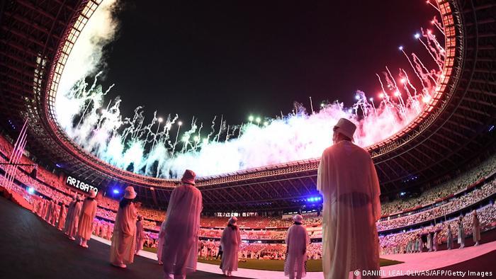 Algumas pessoas, no campo do estádio, observam a queima de fogos de artifício.