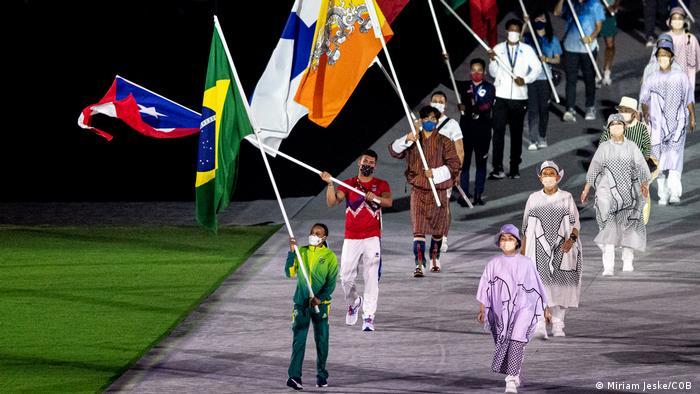 A imagem mostra Rebeca carregando a bandeira brasileira. Ela usa o agasalho do time Brasil. Atrás dela, outras pessoas carregam bandeiras de outros países.