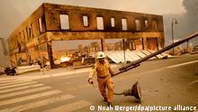 Einsatzleiter Jay Walter zieht einen Laternenmast, der den Highway 89 blockierte, bei den Löscharbeiten eines Waldbrandes, des sogenannten Dixie-Feuers, in der Gemeinde Greenville in Plumas County. Das Feuer zerstörte mehrere historische Gebäude und Dutzende von Häusern im Zentrum von Greenville. +++ dpa-Bildfunk +++