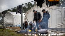 Migrants prepare food at the newly built refugee camp in the Rudninkai military training ground, some 38km (23,6 miles) south from Vilnius, Lithuania, Friday, Aug. 6, 2021. Belarus' border protection agency said Friday that it tightened control along its border with Lithuania to prevent Lithuanian authorities from sending migrants back to Belarus. (AP Photo/Mindaugas Kulbis)
