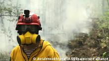 SAKHA REPUBLIC (YAKUTIA), RUSSIA - AUGUST 8, 2021: An employee of the Aerial Forest Protection Service (Avialesookhrana) wears an air-purifying respirator while battling a forest fire in the taiga. Avialesookhrana is a subdivision of Russiaís Federal Agency for Forestry, which monitors and responds to information on forest fire risks. According to Russiaís Emergencies Ministry, 11 wildfires covering an area of more than 50,000 hectares have been extinguished in Yakutia within the last 24 hours. Avialesookhrana Press Office/TASS
