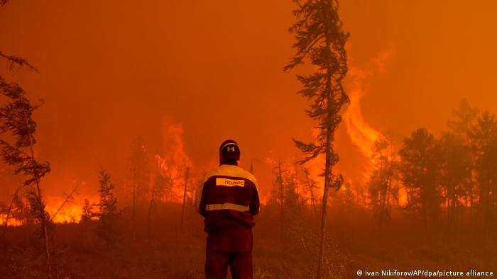 Пожарный близ Якутска смотрит на лесной пожар