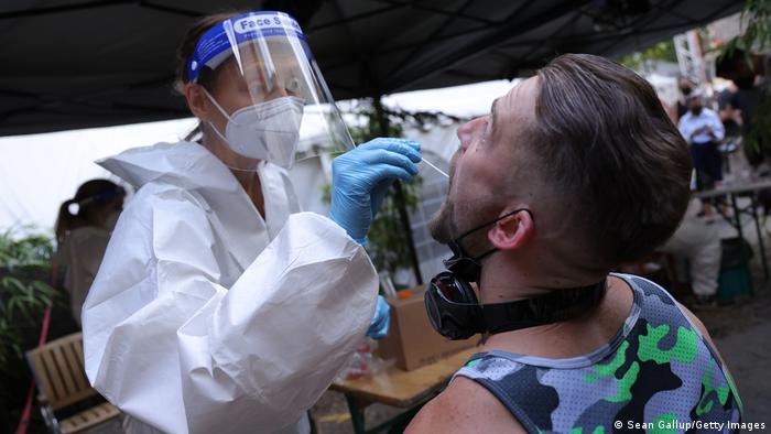 A participant submits for an express PCR test for Covid-19 outside the KiKat Club prior to taking part in an experimental, limited opening of Berlin nightclubs during the coronavirus pandemic on August 06, 2021 in Berlin