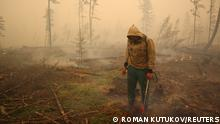 FILE PHOTO: A specialist of the local forest protection service works to extinguish a forest fire near the village of Magaras in the region of Yakutia, Russia July 17, 2021. Picture taken July 17, 2021. REUTERS/Roman Kutukov/File Photo/File Photo