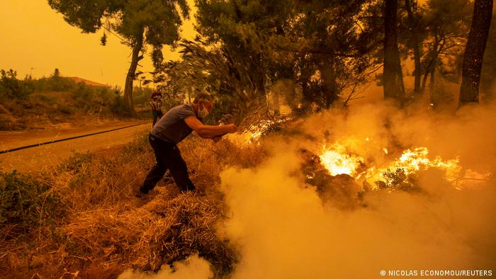A man uses a tree branch to extinguish a wildfire burning in the village of Pefki, on the island of Evia, Greece, August 8, 2021