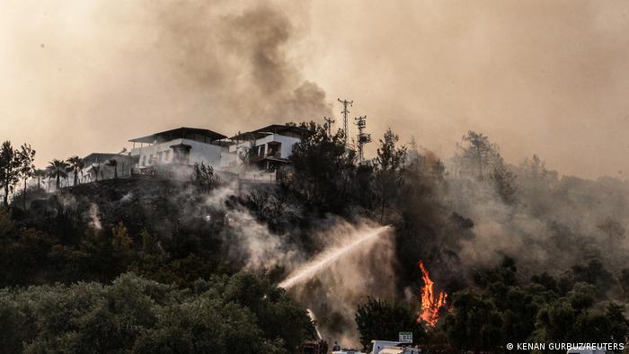 Огонь пылает на холме, где стоят дома