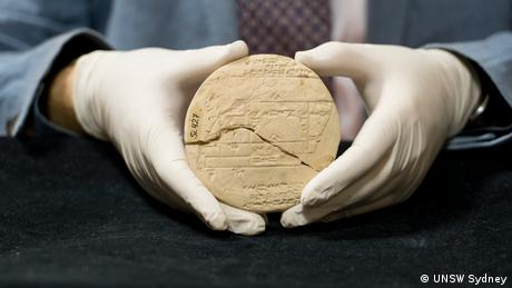 Daniel Mansfield, mathematician at UNSW Sydney holds an Old Babylonian clay tablet, known as Si.427