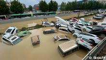 (FILES) This file photo taken on July 21, 2021 shows cars sitting in floodwaters after heavy rains hit the city of Zhengzhou in China's central Henan province. - The death toll from floods in central China rose to 302, officials said on August 2, 2021, after torrential downpours dumped a year's rain on a city in just three days last month. (Photo by STR / AFP) / China OUT