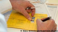 Ein Arzt schreibt am 12.11.2013 in Berlin in einen Impfpass und hält dabei eine Spritze in der Hand.