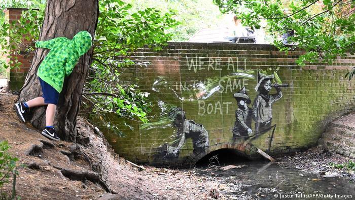 An einer Backsteinwand ist ein Graffiti-Werk des Künstlers Banksy zu sehen. Es zeigt Kinder und den Schriftzug Wir sitzen alle im selben Boot.