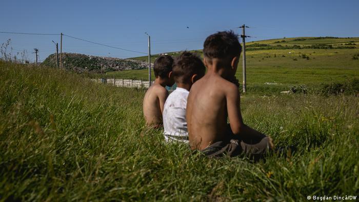 Roma children sit on a grassy hill in Pata Rat, Cluj, Romania