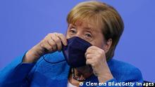BERLIN, GERMANY - AUGUST 10: German Chancellor Angela Merkel puts on her face mask after a press conference after a virtual meeting with German State Premiers about the current coronavirus situation, at the Chancellery on August 10, 2021 in Berlin, Germany. (Photo by Clemens Bilan-Pool/Getty Images)