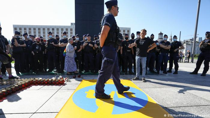 A policeman steps on a banner with the logo of broadcaster TVN modified to resemble a well known symbol of the anti-communist movement in Warsaw Tuesday