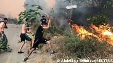 People attempt to put out a fire in the mountainous Tizi Ouzou province, east of Algiers, Algeria August 10, 2021. REUTERS/Abdelaziz Boumzar