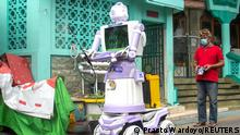 Aseyanto, 53, a resident of the Tembok Gede neighbourhood, operates the Delta Robot, made from household items like pots, pans and an old television monitor, in Surabaya, East Java province, Indonesia, August 7, 2021. The robot is able to perform a number of tasks such as spraying disinfectant, delivering food and meeting the needs of residents who are are self-isolating due to coronavirus disease (COVID-19). Picture taken August 7, 2021. REUTERS/Prasto Wardoyo