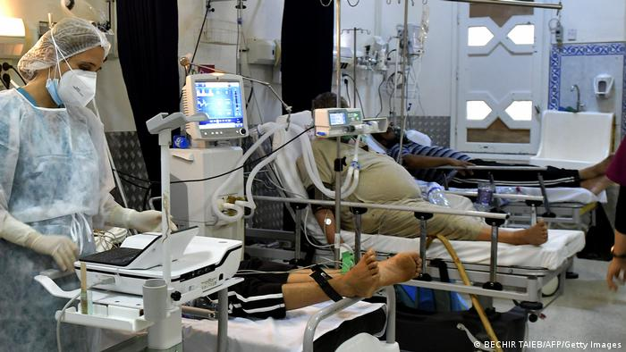 A medic attends to COVID-19 patients as they lie intubated in an ICU in Tunisia's coastal city of Sousse on July 21, 2021