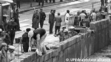 Unter der Aufsicht von bewaffneten Volkspolizisten errichtet eine Ostberliner Maurerkolonne am an der sowjetisch-amerikanischen Sektorengenze am Potsdamer Platz eine Mauer. (zuTV-Dokumentation: Die jüngsten Opfer der Mauer waren noch Kinder) +++ dpa-Bildfunk +++