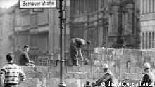 Arbeiter erhöhen die Sektorensperre an der Bernauer Straße in Berlin im August 1961. Fast Abend für Abend war es an diesem und anderen Mauerabschnitten zu Zwischenfällen gekommen. Am 13. August 1961 wurde die Mauer in Berlin gebaut. Foto: dpa (zu dpa: Erinnerung an Mauerbau vor 54 Jahren - Kränze für die Opfer vom 12.08.2015) +++ dpa-Bildfunk +++