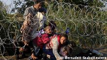 Syrian migrants cross under a fence as they enter Hungary at the border with Serbia, near Roszke, August 27, 2015. Hungary made plans on Wednesday to reinforce its southern border with helicopters, mounted police and dogs, and was also considering using the army as record numbers of migrants, many of them Syrian refugees, passed through coils of razor-wire into Europe. REUTERS/Bernadett Szabo TPX IMAGES OF THE DAY