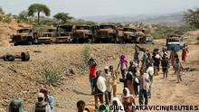 Villagers return from a market to Yechila town in south central Tigray walking past scores of burned vehicles, in Tigray, Ethiopia, July 10, 2021. REUTERS/Giulia Paravicini SEARCH ETHIOPIA FIGHTING FOR THIS STORY. SEARCH WIDER IMAGE FOR ALL STORIES