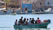Migrants arrives on a boat in the Italian Pelagie Island of Lampedusa on July 29, 2020. - Boats with migrants mainly from Tunisia continue to arrive on the Italian island of Lampedusa. Intercepted by the boats of the Italian costal guard and guardia di finanza police before reaching the shore, migrants are escorted on the Island and transferred to the island's reception centre. (Photo by Alberto PIZZOLI / AFP) (Photo by ALBERTO PIZZOLI/AFP via Getty Images)
