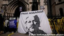 Supporters of WikiLeaks founder Julian Assange hold up a banner as they protest, during the first hearing in the Julian Assange extradition appeal, at the High Court in London, Wednesday, Aug. 11, 2021. Britain's High Court has granted the U.S. government permission to appeal a decision that WikiLeaks founder Julian Assange cannot be sent to the United States to face espionage charges. (AP Photo/Matt Dunham)