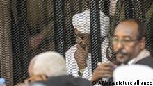 Omar Al-Baschir (M), ehemaliger Präsident des Sudans, sitzt hinter Gittern während seines Prozesses unter Anklage wegen Korruption und Geldwäsche. +++ dpa-Bildfunk +++