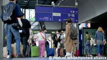 Commuters wait in front of a DB (Deutsche Bahn) helpdesk at the main station in Berlin, Germany, Wednesday, Aug. 11, 2021. A nationwide, two-day train strike has brought big parts of the German railway and commuter system to a standstill. (AP Photo/Michael Sohn)