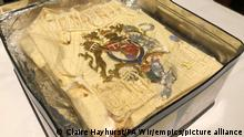 The tin containing plastic wrapped icing of a slice of cake from one of the 23 official wedding cakes made for the Royal Wedding of Prince Charles and Lady Diana Spencer on Wednesday July 29, 1981, which has fetched 1,850 pounds (2,565 dollars US) at auction at Dominic Winter Auctioneers in Cirencester, England, Wednesday Aug. 11, 2021. (Claire Hayhurst/PA via AP)