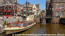 Image of a typical sightseeing boat in a water channel in the inner city of Amsterdam, Holland.