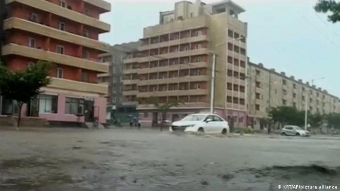 A white car drives through a flooded street with tower blocks in the background