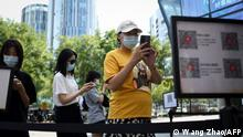 People use their mobile phones to scan a QR health code as a preventive measure against the Covid-19 coronavirus at the entrance of a business district in Beijing on August 10, 2021. (Photo by WANG Zhao / AFP)