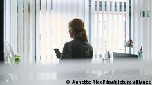 ILLUSTRATION - Eine Frau steht in einem Bürozimmer am Fenster und telefoniert über ein Headset. (gestellte Szene)