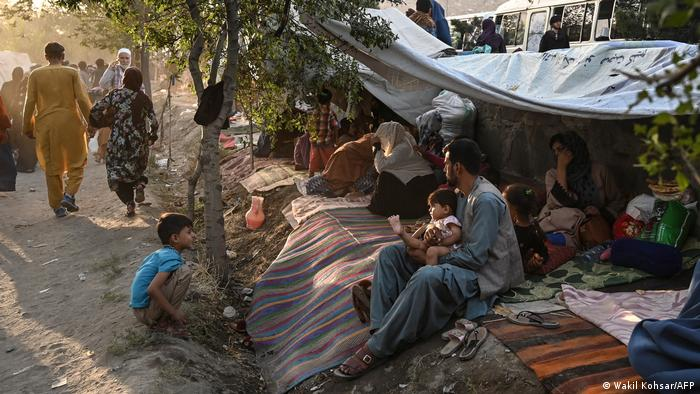 A family sits under a tree and a makeshift shelter holding a young baby
