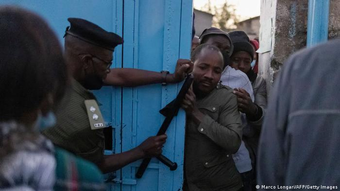A Zambian policeman tries to control the crowd of voters pushing through the gate of a polling station set up in the Matero secondary school in Lusaka