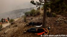 Volunteers from nearby villages rest from watering down a recently burnt part of a forest during a wildfire near Kavaklidere, a town in Mugla province, Turkey, August 5, 2021. REUTERS/Umit Bektas TPX IMAGES OF THE DAY
