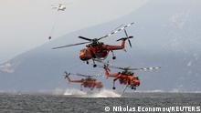 Firefightering helicopters are filled with water off the beach of the village of Pefki, on the island of Evia, Greece, August 10, 2021. REUTERS/Nicolas Economou TPX IMAGES OF THE DAY