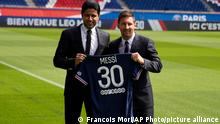 Lionel Messi, right, and PSG president Nasser Al-Al-Khelaifi hold Messi's jersey Wednesday, Aug. 11, 2021 at the Parc des Princes stadium in Paris. Lionel Messi said he's been enjoying his time in Paris since the first minute after he signed his Paris Saint-Germain contract on Tuesday night. The 34-year-old Argentina star signed a two-year deal with the option for a third season after leaving Barcelona. (AP Photo/Francois Mori)
